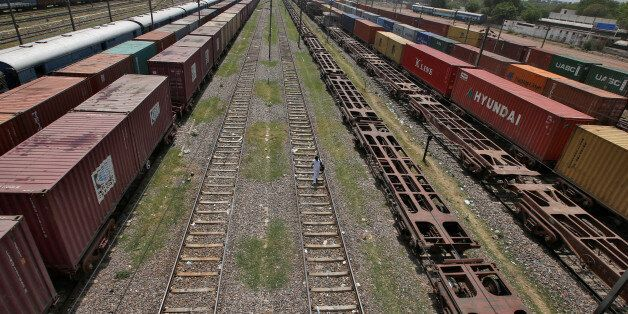 A man walks on a railway track as freight trains are parked at Tughlakabad railway station in New Delhi,...