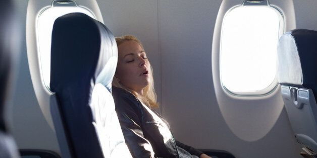 Tired blonde casual caucasian lady napping on uncomfortable seat while traveling by airplane. Commercial transportation by planes.