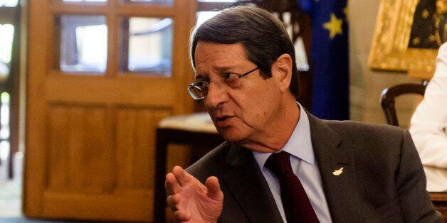 Greek Foreign Minister Nikos Kotzias (L) sits next to Cypriot President Nicos Anastasiades (R) on July...