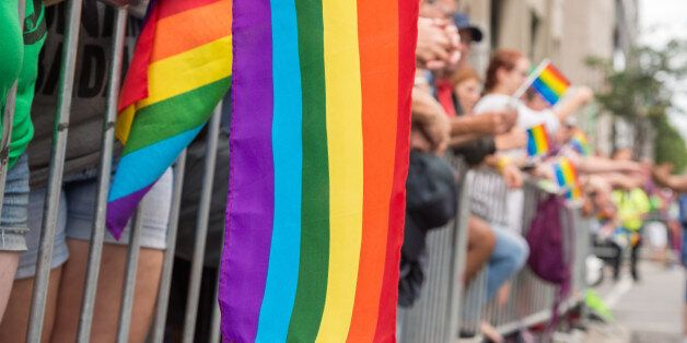Gay rainbow flags at Montreal gay pride parade with blurred spectators in the