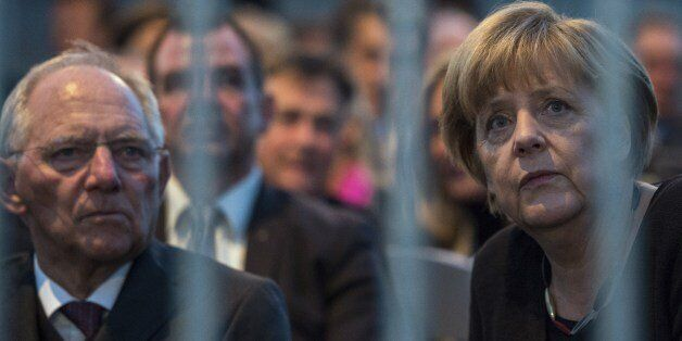 German Chancellor Angela Merkel (R) and German Finance Minister Wolfgang Schaeuble wait for the start...