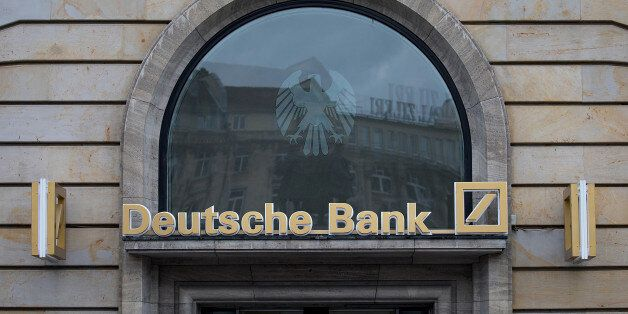 Signage for Deutsche Bank AG sits above a bank branch in Frankfurt, Germany, on Thursday, July 20, 2017....