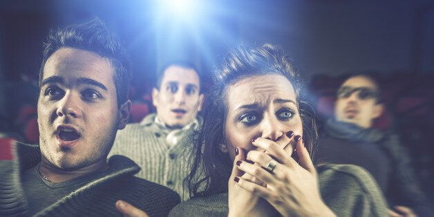 Couple scared at the cinema, watching horror