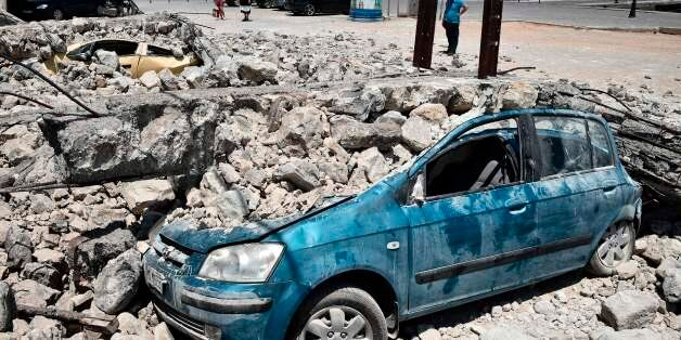 A man looks at cars under rubble on the Kos island on July 22, 2017, following an earthquake which struck...