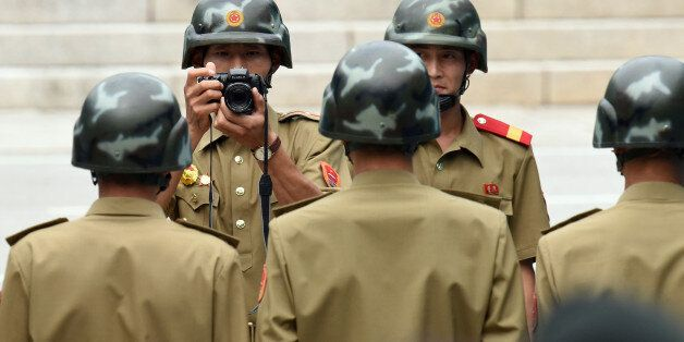 A North Korean soldier takes a group photo of his colleagues as the United Nations Command officials...