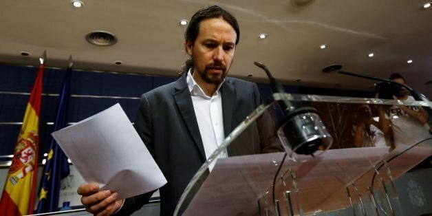 Leader of left wing party Podemos Pablo Iglesias checks a document during a press conference following...