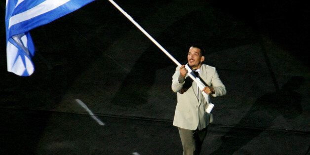 The Greek flag, carried by Piros Dimas, is the first to enter the Olympic Stadium during the opening...