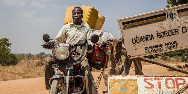 MOYO, UGANDA - FEBURARY 05: A man carrying luggage on his motorbike crosses the border at a formal crossing...