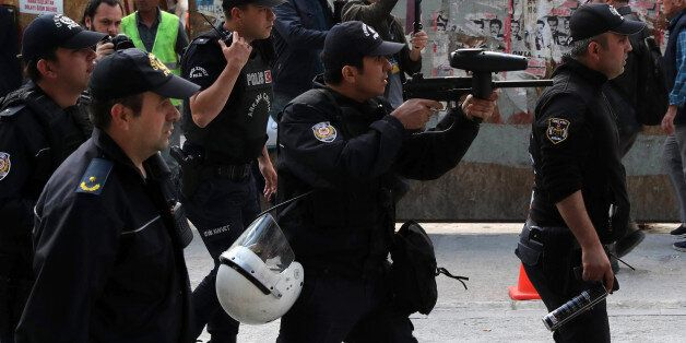 Turkish riot police use tear gas to disperse protesters during a demonstration against the arrest by...