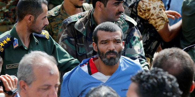 Police officers escort Muhammad al-Maghrabi, 41, who was convicted of raping and murdering a three-year-old...