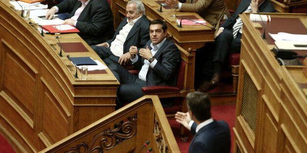 Greek PM Alexis Tsipras (C) gestures listening main opposition leader Kyriakos Mitsotakis delivering...