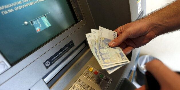 A man withdraws sixty Euros, the maximum amount allowed after the imposed capital controls in Greek banks,...