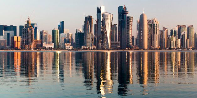 Early morning sunrise golden light hits the city of Doha in Qatar. A wide angle view from across the...
