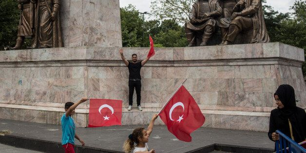 ISTANBUL, TURKEY - JULY 14: People wave Turkish flags while attending a rally to honour the victims of...