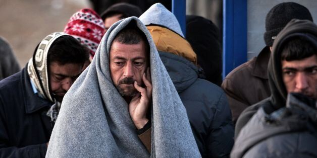 A man with a blanket over his head to protect from the morning cold waits with other migrants and refugess...