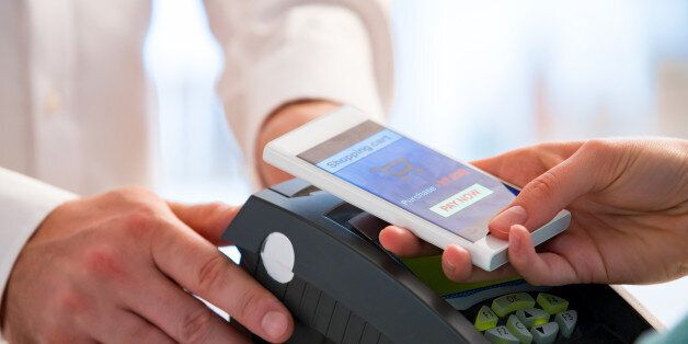 Wireless payment using smartphone and NFC technology. Close up. Customer paying with smart phone in pharmacy....
