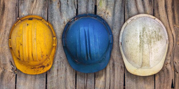 Three vintage construction helmets hanging on an old wooden