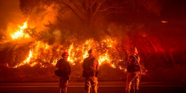 Firefighters monitor flames on the side of a road as the Detwiler fire rages on near the town of Mariposa,...