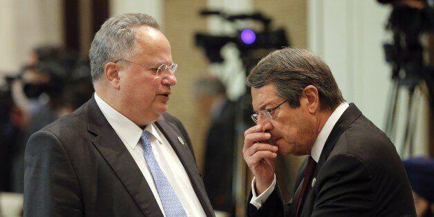 Greek Foreign Minister Nikos Kotzias (L) talks to Cyprus' President Nicos Anastasiades before the opening...
