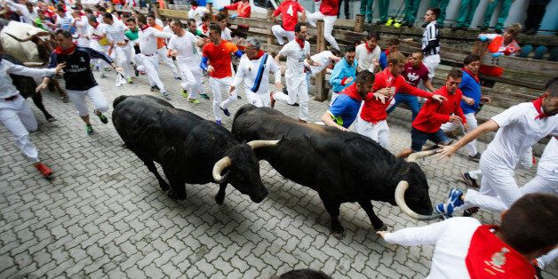 Pamplona, Spain - July 10, 2017: Bulls and people running on the street during the festival of San Fermin....