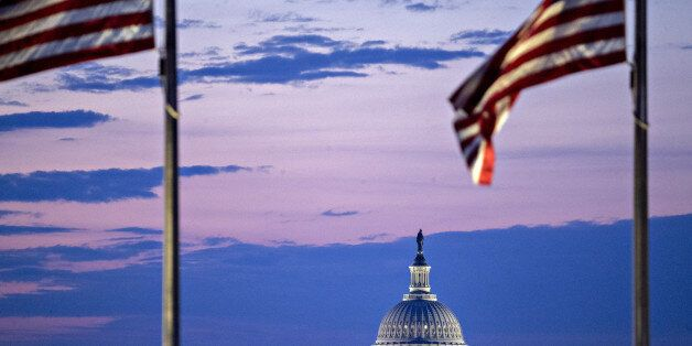 The U.S. Capitol building stands past American flags before sunrise in Washington, D.C., U.S., on Tuesday,...
