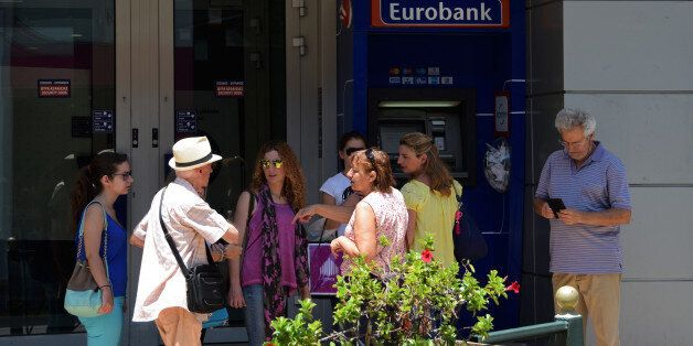 Athens, Greece - July 1, 2015: People waiting at atm machine queue outside a closed greek bank inform...