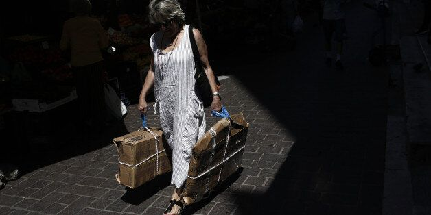 A pedestrian carries packages outside the central meat and fish market in Athens, Greece, on Tuesday,...