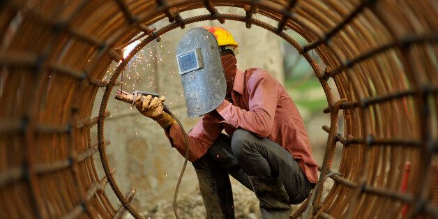 KRISHNA CHAUDHARY, 29yrs old migrated from sunsari, welding iron pillar for on-going Bridge expansion...
