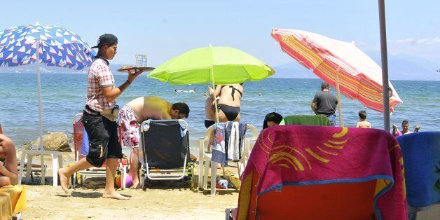 A beach attendant carries a tray of refreshments to holidaymakers at a tourist resort in Stavros, Greece,...