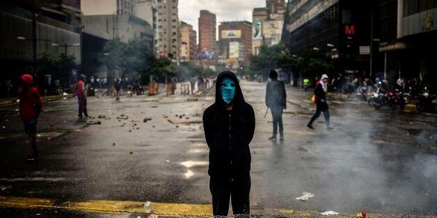 An masked opposition activist takes part in a blockade to protest against Venezuelan President Nicolas...