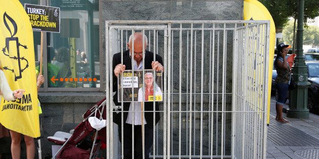 Amnesty International Belgium's Director Philippe Hensmans poses in a cage in front of the Turkish embassy...