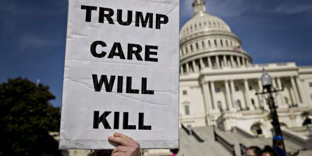 A demonstrator opposed to the Senate Republican health-care holds a sign that reads 'Trump Care Will...