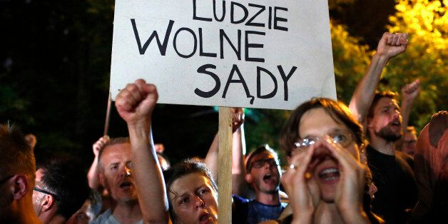 People shout slogans during a protest against supreme court legislation outside the Parliament in Warsaw,...