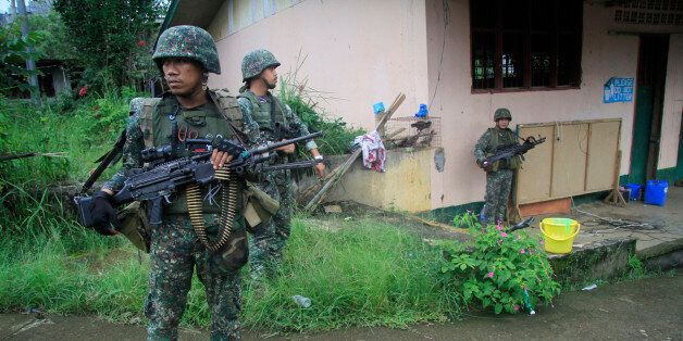 This photo taken on July 12, 2017 shows Philippine troops standing guard prior to a patrol in Marawi...
