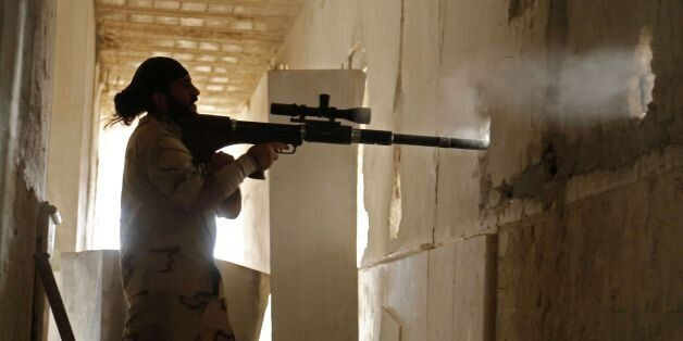 A Syrian rebel fighter from the Faylaq al-Rahman brigade fires a weapon in Ain Tarma, in the eastern...