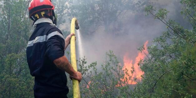 A firefighter uses a hose to spray water as they fight against a fire in Castagniers, near Nice, on July...