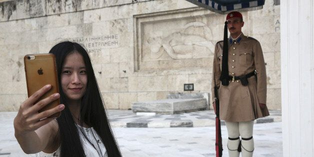 A Chinese tourist takes a photograph of a presidential at the Tomb of the Unknown Soldier on Syntagma...