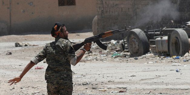 A Kurdish fighter from the People's Protection Units (YPG) fires his rifle at Islamic State militants...