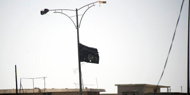 A picture taken on July 1, 2017, shows the black flag of the Islamic State (IS) group moving in the wind...
