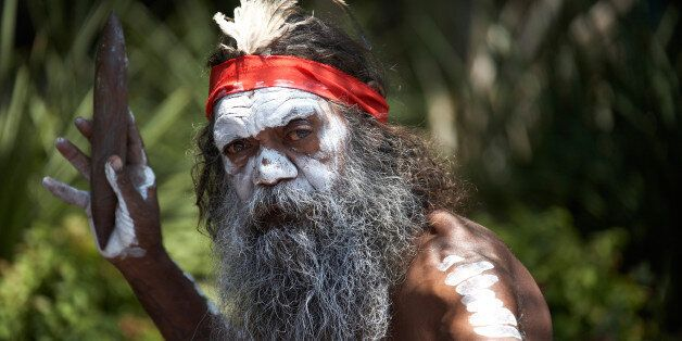 Aboriginal aborigine man with beard and traditional face body paint busking and entertaining visitors...