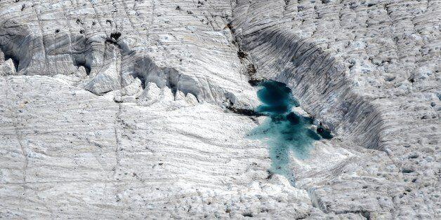 A picture shows water on a melting glacier, next to the 3,135 m Gornergrat (Gorner Ridge) above Zermatt,...