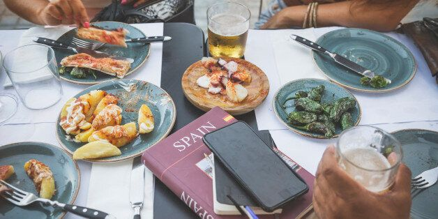 Tourists in Barcelona eating tapas in a typical restaurant in the Barri Gotic. On the table a travel...