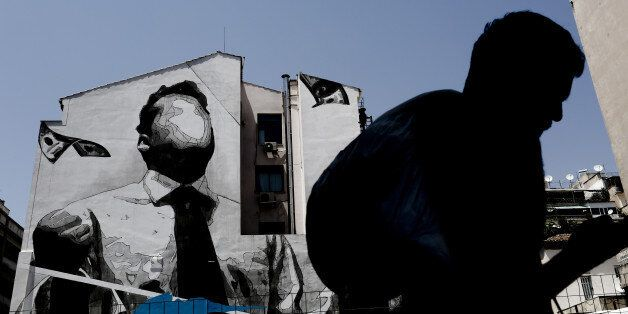 A pedestrian walks past a wall mural by visual artist 'Ino' in Athens, Greece, on Thursday, June 29,...