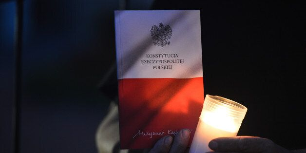 A person holds a copy of Polish Constitution during an anti-government protest - a candle-lit vigil in...