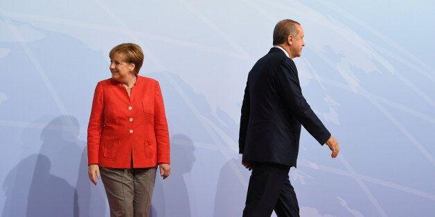 German Chancellor Angela Merkel greets Turkey's President Recep Tayyip Erdogan at the beginning of the...