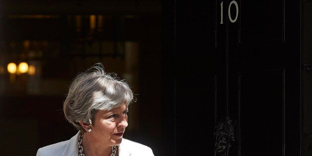 Britain's Prime Minister Theresa May exits 10 Downing Street in central London on July 18, 2017, to greet...