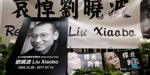 Pro-democracy activists mourn the death of Nobel Laureate Liu Xiaobo, outside China's Liaison Office...