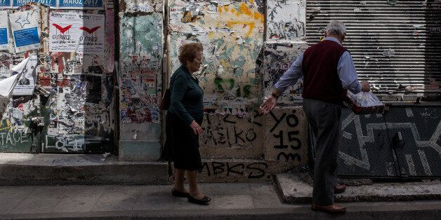 An elderly couple walks in Central Athens in front of closed shops on May 8, 2017. Greece reached an...