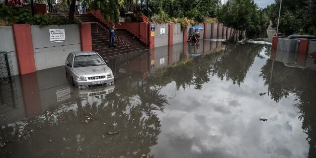 A man takes pictures of a car in a flooded street at the Bayrampasa metro station on July 18, 2017 in...