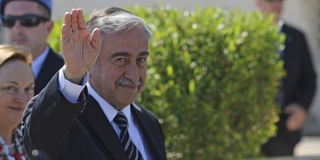 Turkish Cypriot leader Mustafa Akinci waves to journalists at United Nations offices in the buffer zone...